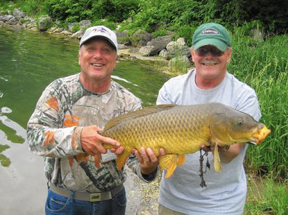 Bob Elias, left, and I yuk it up over this fine carp that I caught when he had to go 'get a sandwich' and let me watch his rods.