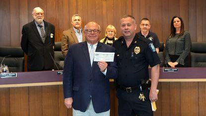 Timothy Ailsworth, front row left, of Local Government Insurance Trust, presents a check for $1,500 to Bel Air Police Chief Charles Moore. Behind them are Commissioners Philip Einhorn, Patrick Richards, Susan Burdette, Brendan Hopkins and Amy Chmielewski.