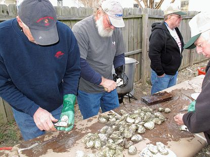 Calvert County Watermen's Association members shuck and steam oysters for MDOWA members before dinner.