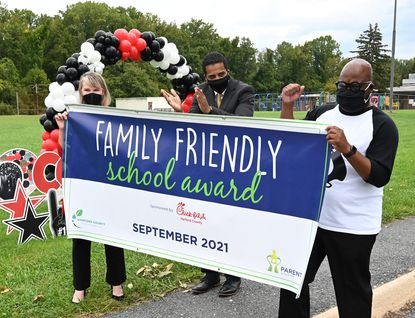 Harford County Pubic Schools representatives Mary Beth Stapleton, left, and Eric Davis, center congratulate William Paca / Old Post Road Elementary Principal Ron Wooden, right with a banner recognizing the first ever Family Friendly School recipient Tuesday, September 28, 2021 at William Paca/Old Post Road Elementary.
