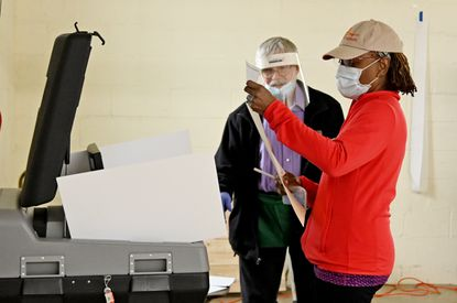 Lois Bennett of Columbia prepares to load her ballot into the scanner at the Howard County Fairgrounds as voting judge Craig Woods watches during a 7th Congressional District special election April 28. Bennett is voting in-person after she accidentally threw her mail-in ballot into a dumpster.