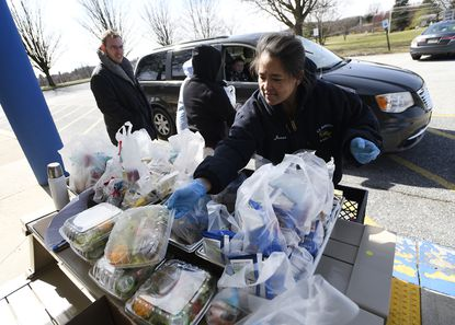 Cris Bailey, right, distributes meals outside Robert Moton Elementary School in Westminster Monday, March 16, 2020. Meals are being distributed for children under 18 years old throughout the county. Bailey, of Uniontown, works at Winters Mill High School. The program was expanded to include breakfast, lunch and dinner by Gov. Hogan on Monday.