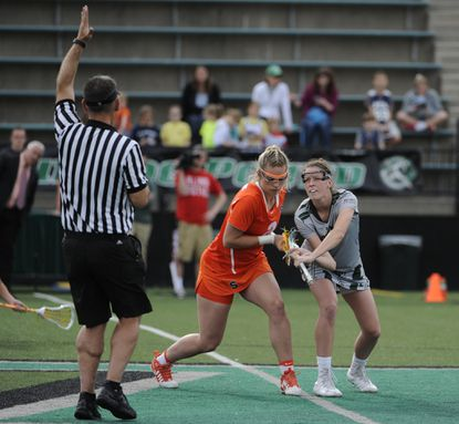 The referee prepares to blow his whistle as Syracuse's Morgan Widner, left, and Loyola's Taylor VanThof are finally in place for a draw in the first half.