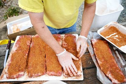 Mike Richter adds a dry rub to ribs at the home of his friend, Paul Sobwick, of Paulie's Cookin', in Columbia.