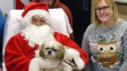 Erich Crouch and her dog Bennie are photographed with Santa during the Manchester Black Friday Christmas Festival at the Manchester fire hall on Friday Nov. 24, 2017.