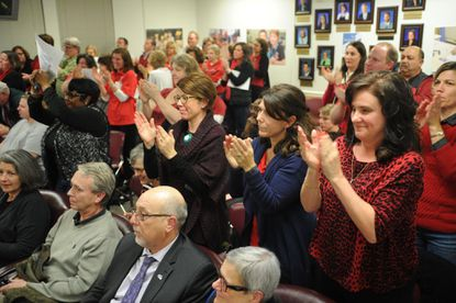 Parents and advocates for Dulaney High School stand and cheer after the Baltimore County Board of Education declined to vote on a contract last year which would have authorized payment for the school's renovation, something some parents opposed.