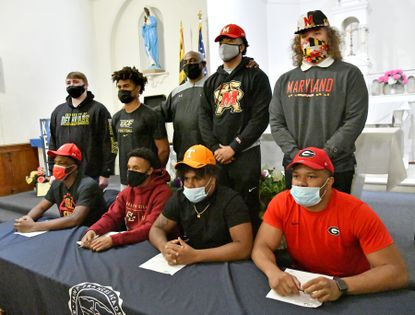 St. Frances football coach Messay Hailemariam, standing at center, poses with his players after the signed national letters of intent to play on Division I teams. Attending the ceremony at the chapel Wednesday evening were (seated, from left) Terrence Butler Jr., Clinton Burton Jr., Aaron Willis and Jamon Dumas-Johnson. Standing with the coach, from left, are Noah Williams, Chad Brown, Zion Shockley and Joe Bearns III.