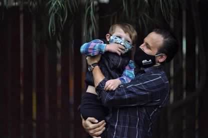 Nicholas Philbrook, right, holds his son Andrew, 4, in his backyard Nov. 18, 2020, in Camarillo, California. Philbrook has been trying to convince court officials that he should be excused from jury duty because his father-in-law, a cancer survivor with diabetes, lives with his family. But court officials told him that is not a valid reason and he must appear in court in early December.