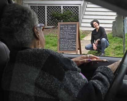 UMBC writer in residence Lia Purpura, right, talks with neighbor Cheryl Curtis after putting out a poem, written by Lucille Clifton, on a chalkboard in front of her house for her neighbors, who are mostly staying home.