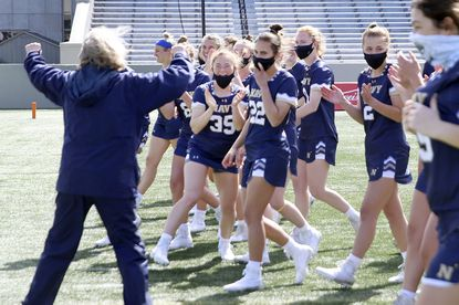 The Navy women's lacrosse team celebrates a 13-12 win against Army on the campus of West Point on March 27. The wearing of masks and regular COVID-19 testing has become the norm for midshipmen athletes, and testing will continue throughout the spring despite mass vaccinations of the brigade.