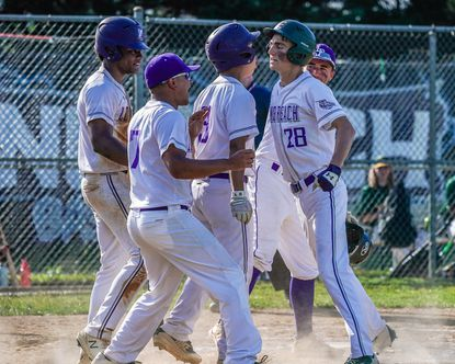 Long Reach players celebrate with Brendan O'Reilly (28) after his three-run home run in the first inning of the Lightning's 13-1 playoff win over Wilde Lake on Monday, June 7, 2021.