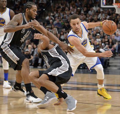 Warriors guard Stephen Curry drives around Spurs' Kawhi Leonard and Patty Mills during the first half on Sunday, April 10, 2016, in San Antonio.