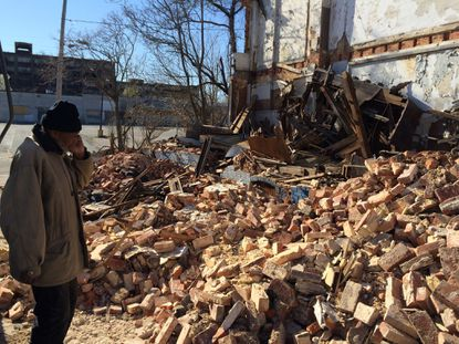 Robert English considers the rubble from a West Baltimore row house that collapsed Monday on his cousin's car. His cousin, Thomas Lemmon, was in the car and died Monday, firefighters said.