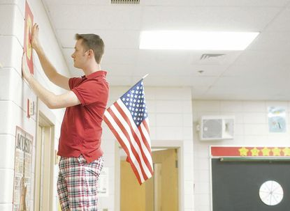 """Triadelphia Ridge Elementary School music teacher Matthew Flynn hangs posters that will spell out the word """"caring,"""" one of the school's traits for students to follow. Flynn has been a teacher at the school for six years."""