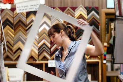 In 2005, Laurel Art Center employee Mo Trafton works on a framing job at the Main Street store.