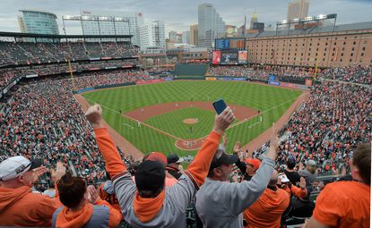 Fans celebrate after Oriole Jonathan Villar homered in the first inning of the Baltimore Orioles' home opener against the New York Yankees at Oriole Park at Camden Yards. April 4, 2019.