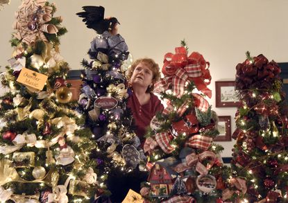 Cindy Potee puts the finishing touches on holiday trees at The Shephard's Staff's Festival of Trees at John Street Quarters in Westminster last year.