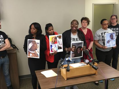 Kelly Holsey Davis, the wife of Keith Davis Jr. (center, holding single picture of her and her husband) has been a vocal critic of Baltimore police and prosecutors. Photo by Jessica Anderson, Baltimore Sun