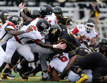 Towson running back Darius Victor(7) scores a touchdown as St. Francis defensive lineman Erik Walker(2) tries to stop him in the first quarter in Towson on Saturday, Sept. 12, 2015.