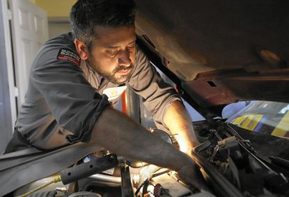 Mechanic Chris Geropoulos works on a car in Chicago's Belmont Heights neighborhood.