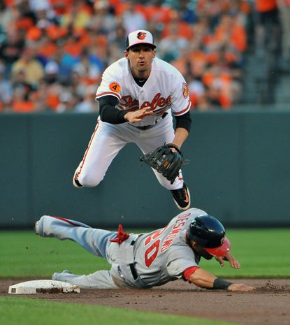 Orioles second baseman Ryan Flaherty forces out Washington's Ian Desmond and throws to first to double-up Tyler Moore in the second inning Wednesday night.