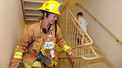 Wendy McCord, a firefighter from Howard County, climbs stairs at a Baltimore hotel in 2012, during a commemoration for firefighters killed on 9/11. The Howard County Council voted on March 5 to update the county's charter to refer to all firemen and firewomen as firefighters.