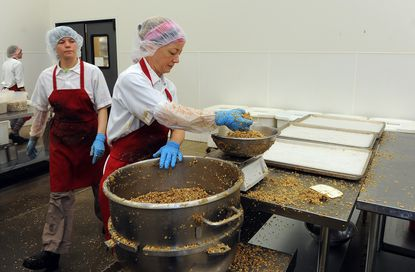 Timonium, MD -- Molly Cruse, a bakery production assistant, measures ingredients at Michele's Granola, which is now located at a larger warehouse facility due to the company's success.