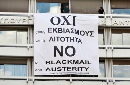"""Employees adjust a banner reading """"No to blackmail and austerity"""" at the Finance Ministry in central Athens on July 1, 2015."""