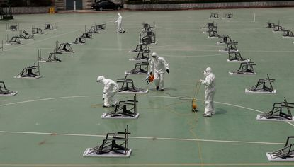 Workers wearing protective gears spray disinfectant at desks and chairs before an insurance planner qualification exam in Seoul, South Korea, Saturday, April 25, 2020. The General Insurance Association of Korea held a qualification exam while maintaining social distancing at the outdoor as a part of precaution against the new coronavirus and also all applicants had to wear face masks and had their temperature checked. (AP Photo/Lee Jin-man)