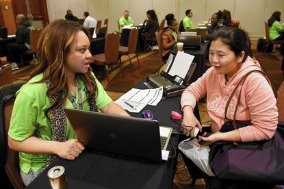 Certified navigator Athena Lynch, left, works with Tenzin Paldon of White Marsh, who was renewing her insurance at the Health Care Access Maryland enrollment fair held at the Hyatt Regency at the Inner Harbor.