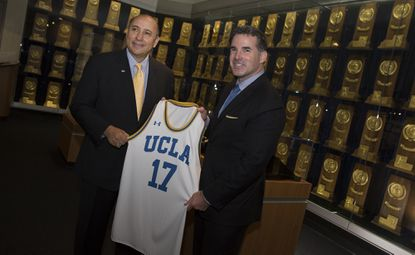 LOS ANGELES, CALIF. -- UCLA athletic director Dan Guerrero, left, and Under Armour's Kevin Plank, right, with a UCLA jersey following a meeting and prior to a press conference at the Morgan Center where they will officially announce UCLA and Under Armour agreement on the largest apparel deal in college sports: 15 years, $280 million in Los Angeles, Calif., on May 24, 2016.