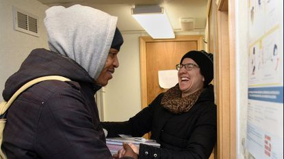 Michael Washington, left, of Baltimore says goodbye to nurse Elizabeth Spradley, right, in the Behavioral Health Leadership Institute REACH van, which is parked outside the Baltimore City Central Booking facility.