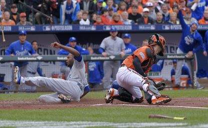 Kansas City Royals center fielder Lorenzo Cain, left, scores in front of Orioles catcher Caleb Joseph in the first inning of Game 2 of the American League Championship Series at Camden Yards.