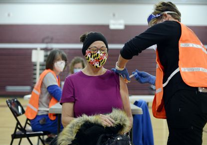 Kelli Eger, the cafeteria manager of Winfield Elementary School, gets her second dose of the Moderna COVID-19 vaccine from Piney Ridge Elementary School nurse Tiffany Yetman, right, during a vaccination clinic for CCPS educators and staff at Winters Mill High School on Wednesday, Feb. 17, 2021.