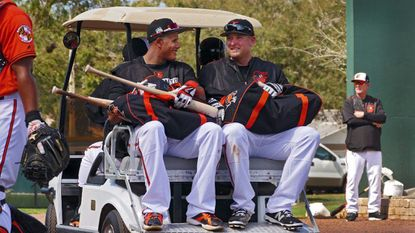 Manny Machado (left) smiles while talking with Mark Trumbo as they get a ride from the batting cages to the practice fields with manager Buck Showalter during spring training at the Ed Smith Stadium baseball complex in Sarasota this past spring.
