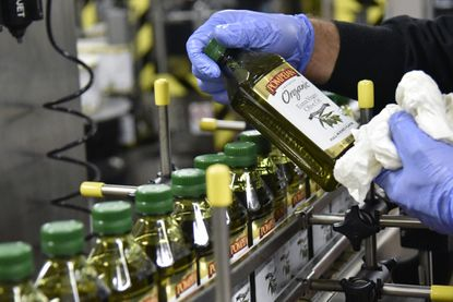 Baltimore, Md -- Fulvio Domenicali, production manager, Pompeian Olive Oil Company, holds a bottle of Organic Extra Virgin Olive Oil. Pompeian is entering a partnership with the DCOOP Group of Spain, a cooperative of olive growers.
