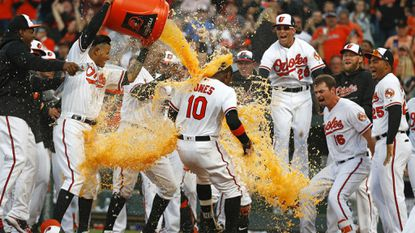Teammates greet Baltimore Orioles' Adam Jones (10) at home plate after he hit a solo home run to end an opening day baseball game against the Minnesota Twins, Thursday, March 29, 2018, in Baltimore.