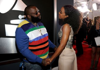 Rick Ross (left) shares a moment with Kelly Rowland on the Grammys red carpet.