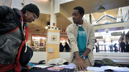 Jane Nesbitt of West Baltimore listens to Eean Logan, director of civic culture and youth programs with No Boundaries Coalition, as a group of community organizations are conducting a citywide survey at Lexington Market, to track Baltimore residents' policy priorities Thu., Nov. 14, 2019 — the largest issue-oriented survey in city history. (Karl Merton Ferron/Baltimore Sun Staff)