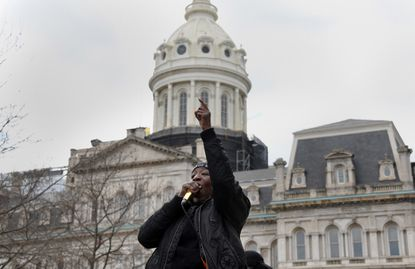 Angel Selah of Baltimore leads a chant in front of City Hall as part of a car caravan that started on Ednor Road and traveled to City Hall to join in solidarity with nationwide protests to support the demands of families of victims of police brutality.
