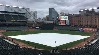 A tarpaulin covers the infield Tuesday afternoon at Camden Yards. The postponed game against the Tampa Bay Rays will be made up as part of a single-admission doubleheader May 12 starting at 3:05 p.m.