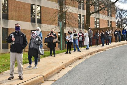 Baltimore County Public Schools central office staff form a line that wraps around Building E on the Greenwood campus to get their computers checked for malware. Online classes were shut down last week by ransomware, but will resume Wednesday.