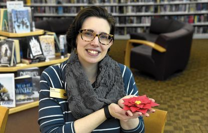 Erin Terwilliger, instruction and research specialist at the Howard County Public Library in Glenwood, will be teaching a class called Art Escape: Paper Poinsettias, on December 12 at the library. Here, she holds one of the paper flowers which she is crafting.