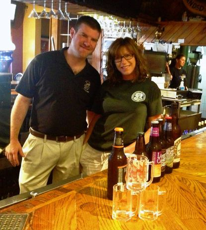 Dan Feehan, general manager of E.W. Beck's Restaurant & Pub, and Ivy Wells, Main Street and Economic Development Director for the town of Sykesville, pose with some of the craft beers and commemorative glassware for the Sept. 8 Chili Cookoff and Craft Beer Festival at the pub's Main Street parking lot.