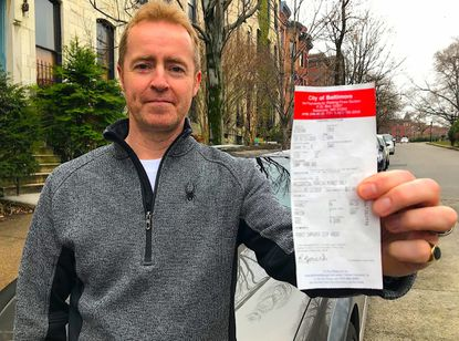 Robert Bunch of Bolton Hill in Baltimore is protesting a $52 fine for displaying a city-issued parking permit on the passenger side of his car's dashboard