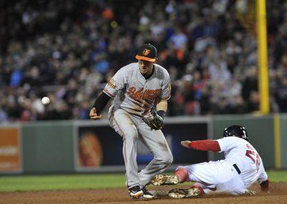 Orioles shortstop Ryan Flaherty mishandles the ball and Boston Red Sox third baseman Brock Holt (26) is safe at second base.