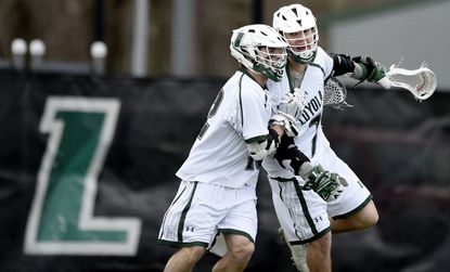 Loyola midfielder Jeff Chase, left, celebrates his goal with teammate Pat Spencer during the third quarter. It was Chase's second goal of the game. Loyola went on to beat Johns Hopkins 9-8 at Ridely Athletic Complex.