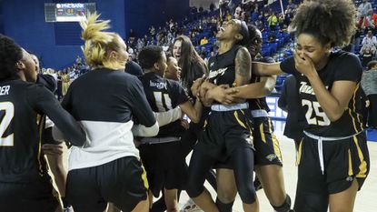 Towson forward Nukiya Mayo (1) gets a hug from her teammate as they celebrate their 53-49 win over Drexel in an NCAA college basketball game in the championship of the Colonial Athletic Association tournament, Saturday, March 16, 2019, in Newark, Del.