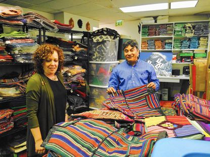 Nancy Scheinman looks on as Season Shrestha shows fabric that he bought from Nepal. They are spearheading the Rotary Club of Towsontowne's relief efforts on behalf of Nepal, an already poor nation that is trying to recover from an earthquake.
