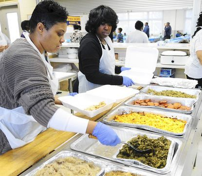 Neet Diggs, of Havre de Grace, left, and Valorie Colby, of Belcamp, begin to make to-go meals during the Aberdeen Community Dinner sponsored by the Evangelistic Church of Deliverance Thanksgiving Day.